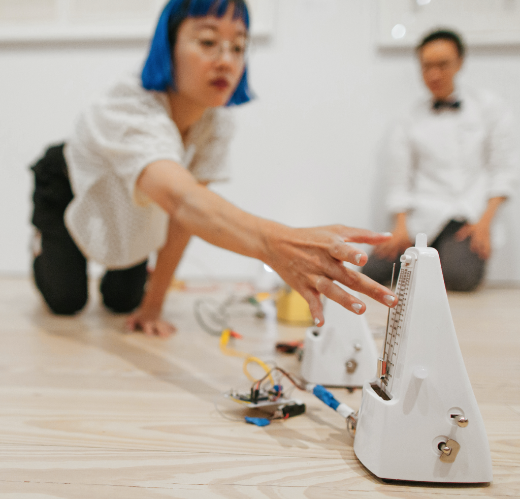 Christine Sun Kim starts a metronome for a performance piece