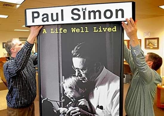 """Walter Ray (left) and Aaron Lisec set up the exhibit """"Paul Simon: Compassion, Vision, Courage"""" Thursday at Tri-Township Public Library in Troy. PHOTO BY JOHN SWISTAK, JR."""